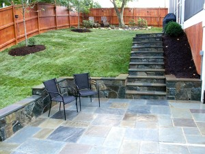 Flagstone patio with stone seating wall and stone steps leading to back porch