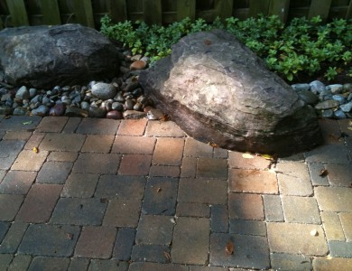 Boulder set into paver patio in McLean.