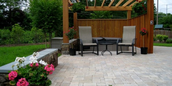 Paver patio with building stone seating wall and hot tub area in Falls Church.