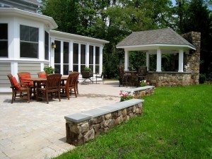Paver patio with outdoor bar and grill and building stone seating wall in Falls Church.