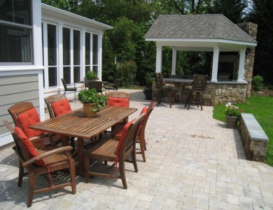 Paver patio with outdoor bar and grill kitchen and building stone seating wall in Falls Church.