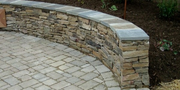 Paver patio with building stone seating wall in North Arlington.
