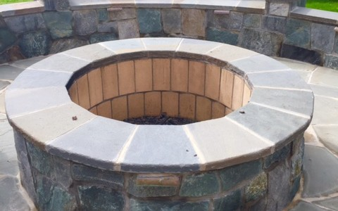 Patio with a flagstone fire pit with built-in seating and lighting in McLean, VA