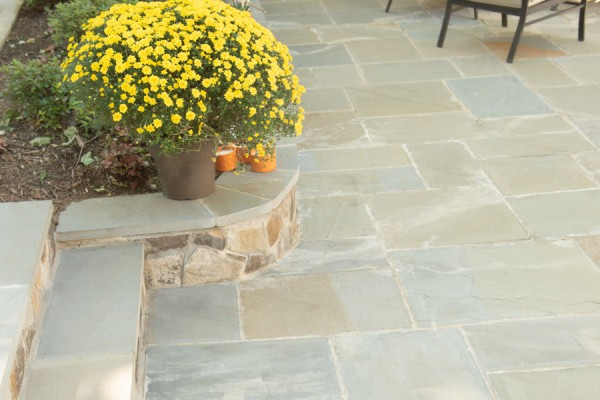 Outdoor stone patio design and installation with steps and retaining walls.