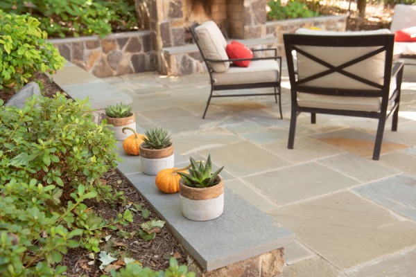 Stone patio with retaining wall seating, patio furniture and stone fireplace